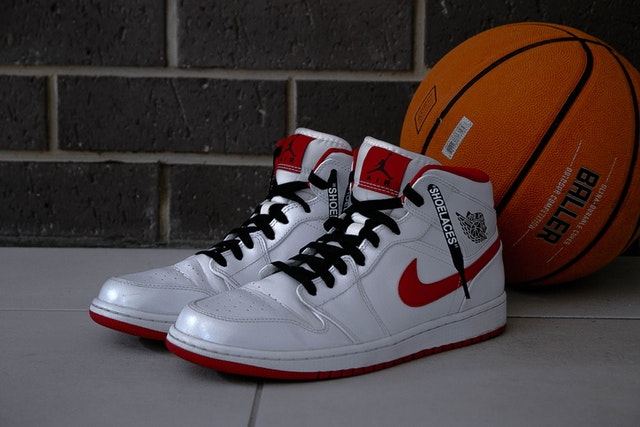 A pair of Nike sneakers and a basketball behind them.