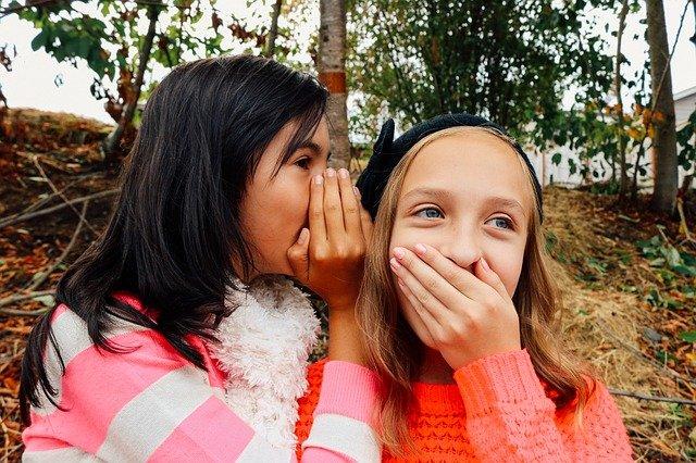 Two girls whispering secrets.